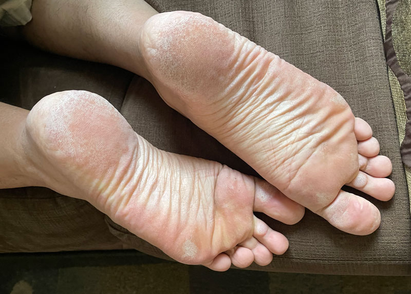 Masculine male bare feet on grass
