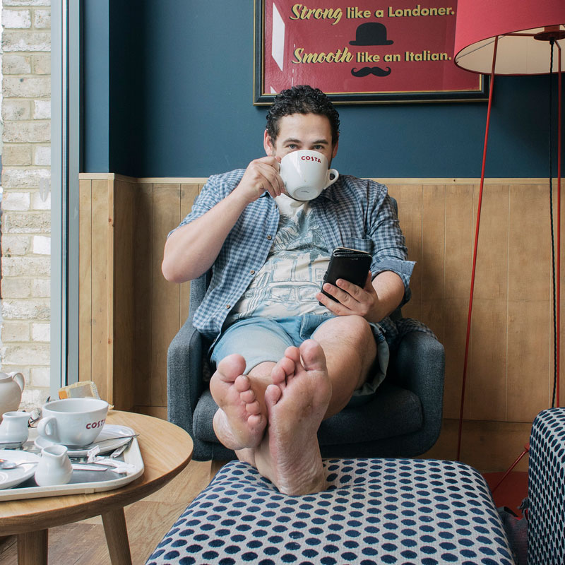 Man showing off his beautiful bare soles at a coffee shop